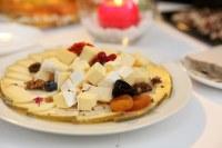 Bodegón de quesos con frutos secos, flores y aromáticos